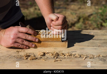 Hands of a carpenter planed wood planes, work on nature - Stock Photo