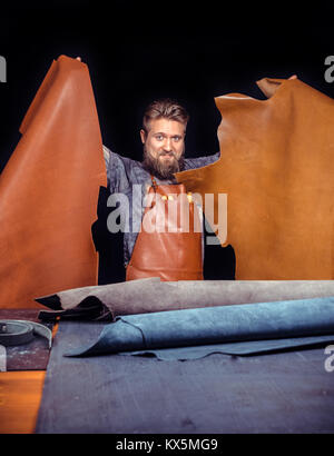 Leather Artist processes a workpiece from leather in studio - Stock Photo