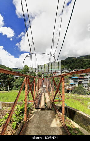 The suspension or hanging bridge in Banaue connects the downtown market area with the Batad road-used by many students - Stock Photo