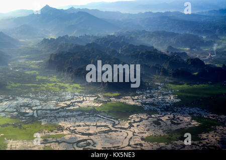 Karst mountain in Maros in aerial drone view with mount Bawakaraeng in the background. - Stock Photo
