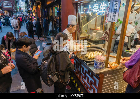 People buying pan fried Shanghai dumpling at a food stall - Stock Photo