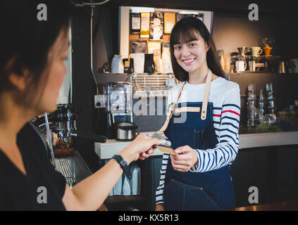 customer pay coffee drink with credit card to barista at counter bar in cafe,Food and drink business,billing payment