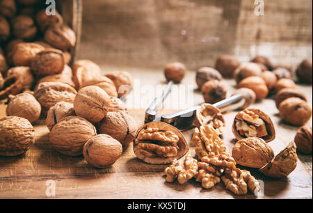 Walnuts and an old nutcracker on a table - Stock Photo