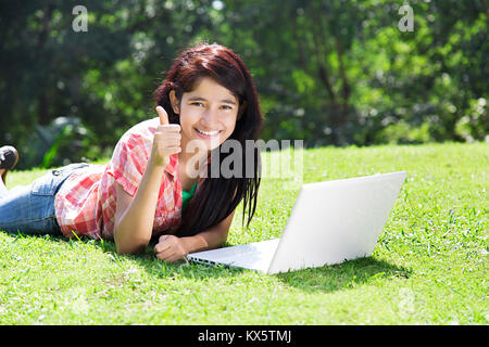 1 Indian Teenager Girl Lying Grass Using Laptop Chatting Park - Stock Photo