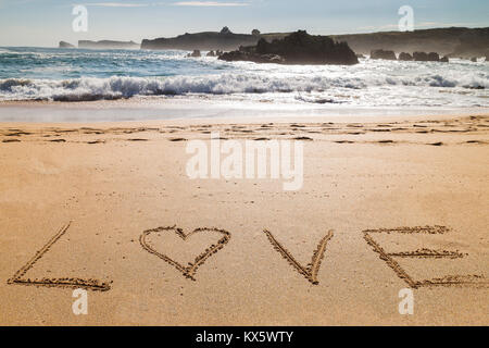 word love written on the seashore in the sand of a beautiful beach - Stock Photo