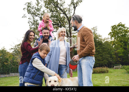 Big happy family with labrador dog spending time together in park - Stock Photo