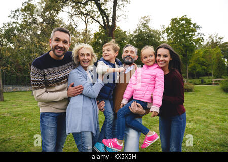 Cheerful big family spending time together in park - Stock Photo