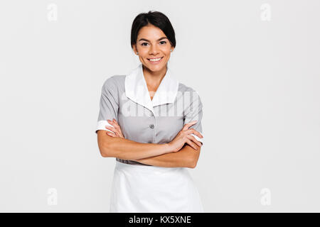 Close-up portrait of young smiling housekeeper in uniform standing with crossed hands and looking at camera, isolated - Stock Photo