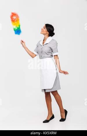 Full length photo of tidy female housekeeper in uniform swipes with dust cleaner, isolated on white background - Stock Photo