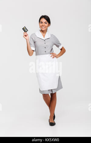 Full length photo of pretty brunette housekeeper standing with hand on her waist and holding credit card, isolated - Stock Photo