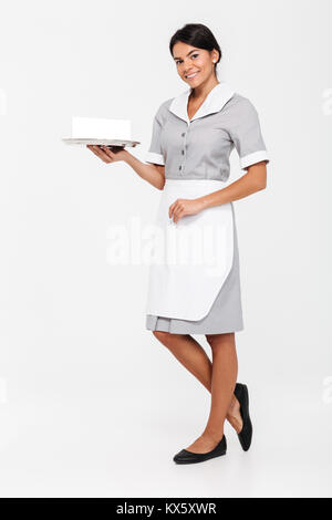 Full length photo of young attractive woman in uniform holding metal tray with empty sign card while standing and - Stock Photo