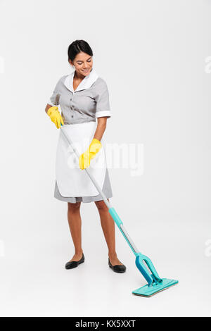 Full length photo of happy housekeeper in uniform cleaning floor with mop, isolated on white background - Stock Photo