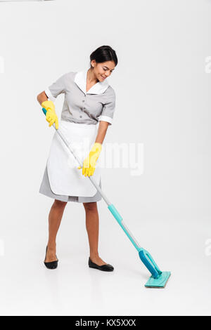 Full length portrait of young attractive woman in uniform cleaning floor with mop, isolated over white background - Stock Photo