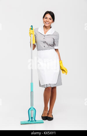 Full length portrait of cheerful brunette girl in uniform and rubber gloves standing and holding mop, isolated on - Stock Photo