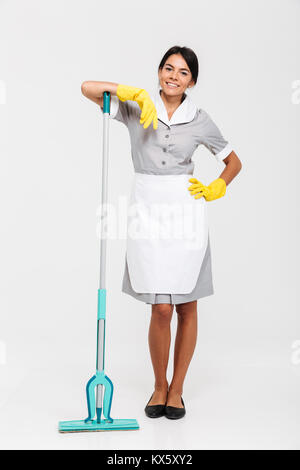 Full length photo of attractive brunette maid in uniform leaned on mop while standing and looking at camera, isolated - Stock Photo