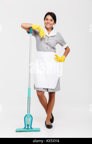 Full length photo of smiling brunette maid in uniform and rubber gloves leaned on mop while standing and looking - Stock Photo
