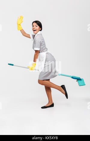 Full length photo of happy funny girl in uniform riding mop as a witch, isolated over white background - Stock Photo