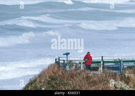 A man wearing a red jacket standing on a viewing platform overlooking the sea in Newquay Cornwall - Stock Photo