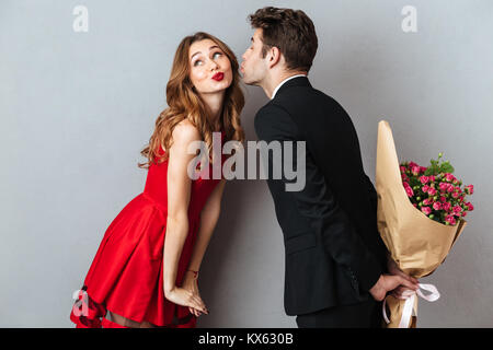 Portrait of a young lovely couple kissing while standing and holding flower bouquet over gray wall background - Stock Photo