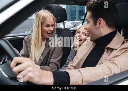 Picture of cheerful young man sitting in car with his wife and daughter. Looking aside. - Stock Photo