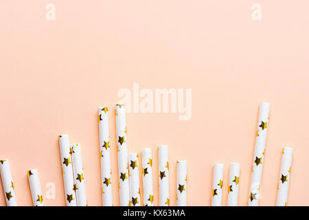 Elegant White Paper Drinking Straws with Golden Stars Pattern Scattered as Border Frame on Pink Peachy Background. - Stock Photo