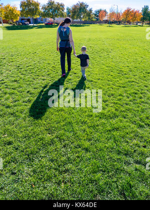 Mother and two-year old son walking together holding hands, walking away, casting long shadows, on green grass in - Stock Photo