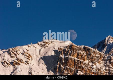 Scenic picture of a big full moon over the Faloria mountain, Cortina D'Ampezzo, Italy - Stock Photo