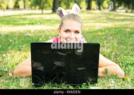 cute woman lying on grass and peeking behind laptop in park - Stock Photo