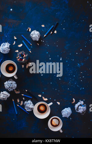 Dark background with crumpled paper balls, empty coffee cups, pencils, paper, notes and notepads. Still life with - Stock Photo