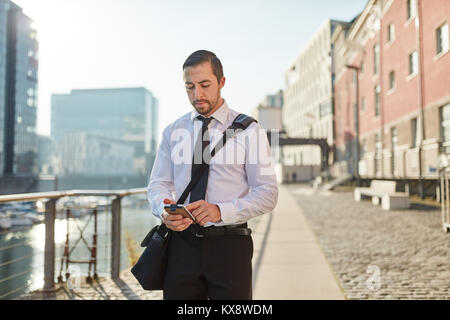 Young businessman typing SMS on smartphone while walking home - Stock Photo