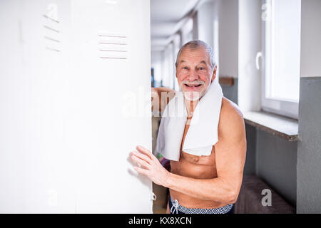 Senior man standing by the lockers in an indoor swimming pool. - Stock Photo