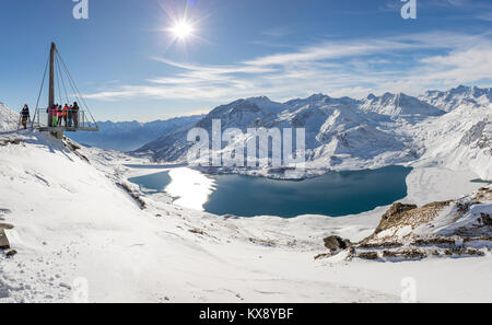 VAL CENIS, FRANCE - DECEMBER 31, 2017 : People enjoying views of Mont Cenis lake and the surrounding mountains from the platform on the Col de la Met,