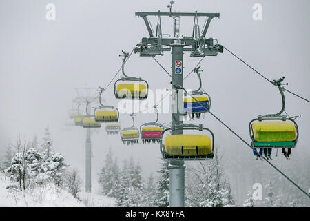 Ski chairlift bringing skiers and snowboarders up the Skrzyczne mountain after heavy snowfall on a misty winter - Stock Photo