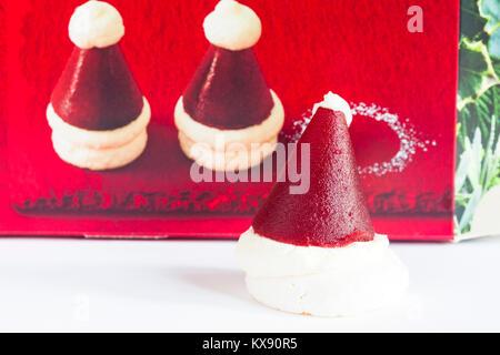 M&S mini Santa hats - crisp meringue base topped with vanilla cream and raspberry jelly - Stock Photo