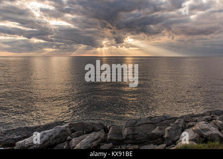 Sun rays shining through dark storm clouds over the ocean with rocks in the foreground. Taken on Cape Breton Island, - Stock Photo