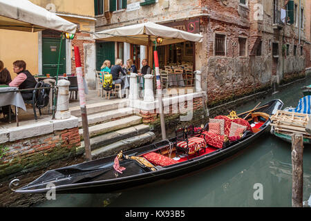 A gondola parked beside a canal side restaurant in Venice, Italy, Europe. - Stock Photo