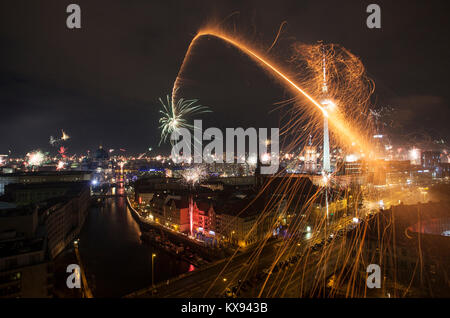 Fireworks explode in the Mitte of Berlin during the celebration of New Year Eve. The new year in Germany is popularly - Stock Photo