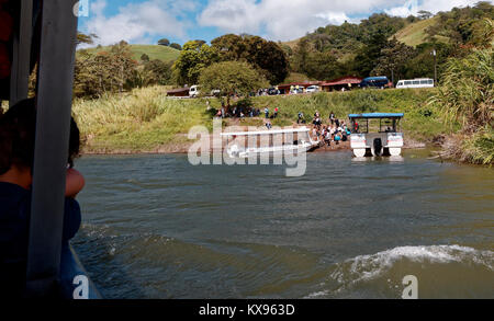 Tourist leaning on side of boat ferrying passengers from La Fortuna land at Monteverde, across Lake Arenal, Costa - Stock Photo