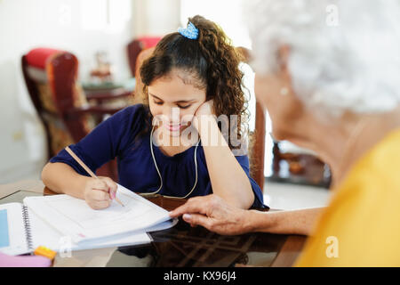 Elderly Woman Helping Little Girl Doing School Homework - Stock Photo