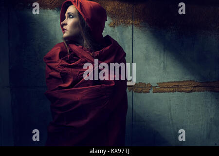 Young woman wrapped in red cape and hood - Stock Photo