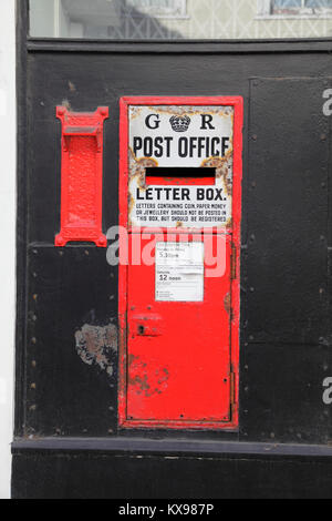 Old GR red letter box and stamp vending machine in the wall of an old Post Office (now closed) in Hastings Old Town - Stock Photo