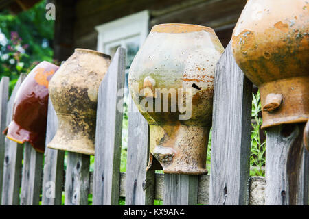 Old broken clay jugs on wooden fence in rural environment - Stock Photo