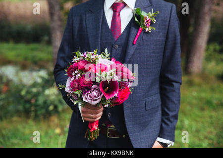 Elegant groom in costume and bow-tie with bouquet . - Stock Photo