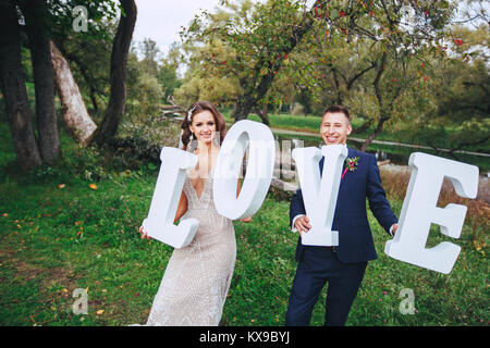 Happy wedding couple holding big white love letters and kissing - Stock Photo