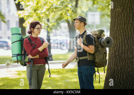 Teenagers tourists with backpacks - smoking and standing in the park at summer midday - Stock Photo