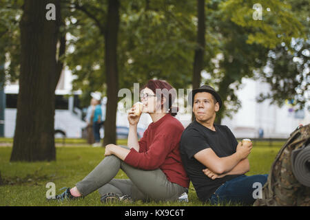 Couple of teenagers tourists with backpacks eating ice cream and have rest in the city park - Stock Photo