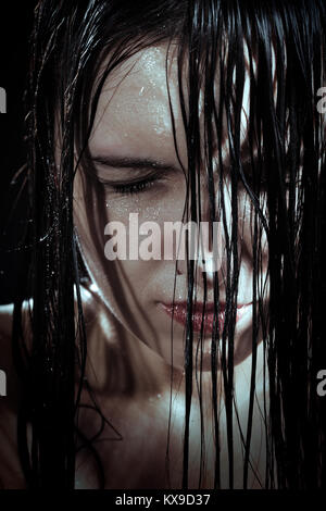 serious sad woman with wet black hair close her eyes in dark - Stock Photo