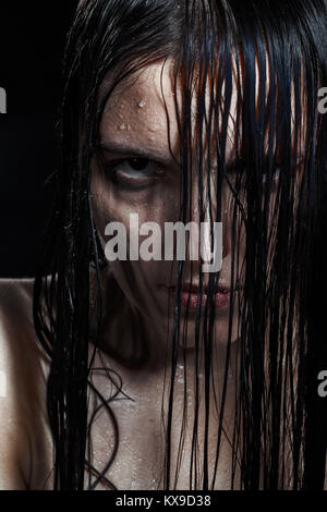 serious angry woman with wet black hair looking at camera - Stock Photo