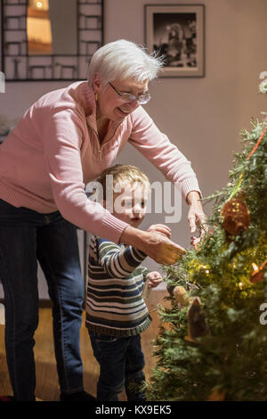 Wheat Ridge, Colorado - Susan Newell, 69, helps her grandson, Adam Hjermstad Jr., 3, decorate the Christmas tree. - Stock Photo