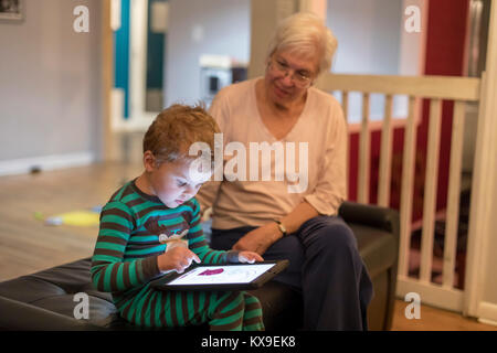 Wheat Ridge, Colorado - Susan Newell, 69, watches as her grandson, Adam Hjermstad Jr., 3, plays an educational game - Stock Photo